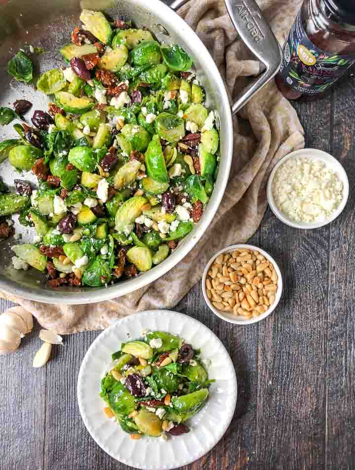 pan and white plate with Mediterranean low carb Brussels sprouts and bowls of pine nuts and feta