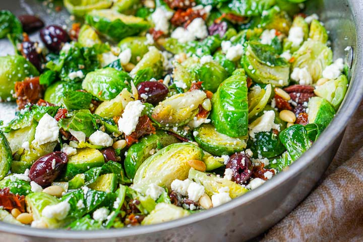 closeup of the pan with sautéed Brussels sprouts, olives, feta and sun dried tomatoes