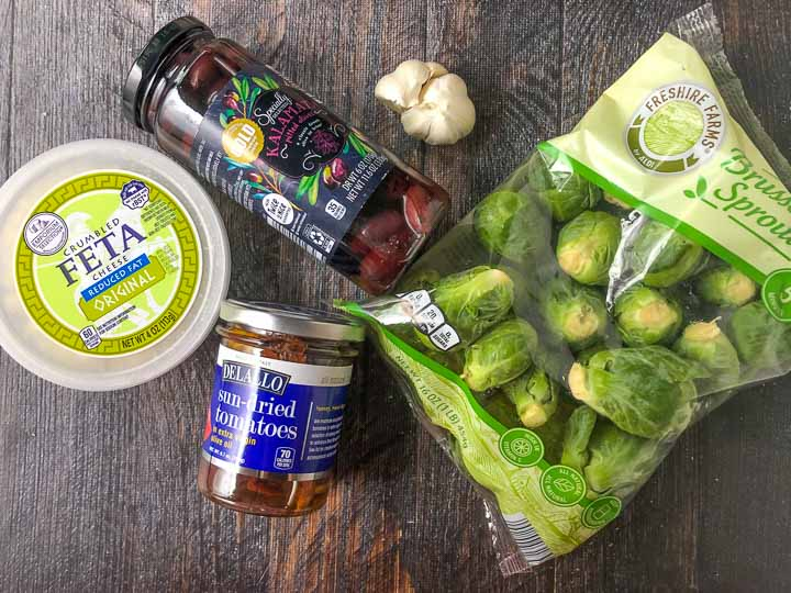 mediterranean brussels sprouts ingredients: kalamata olive, garlic, feta, sun dried tomatoes and Brussels sprouts