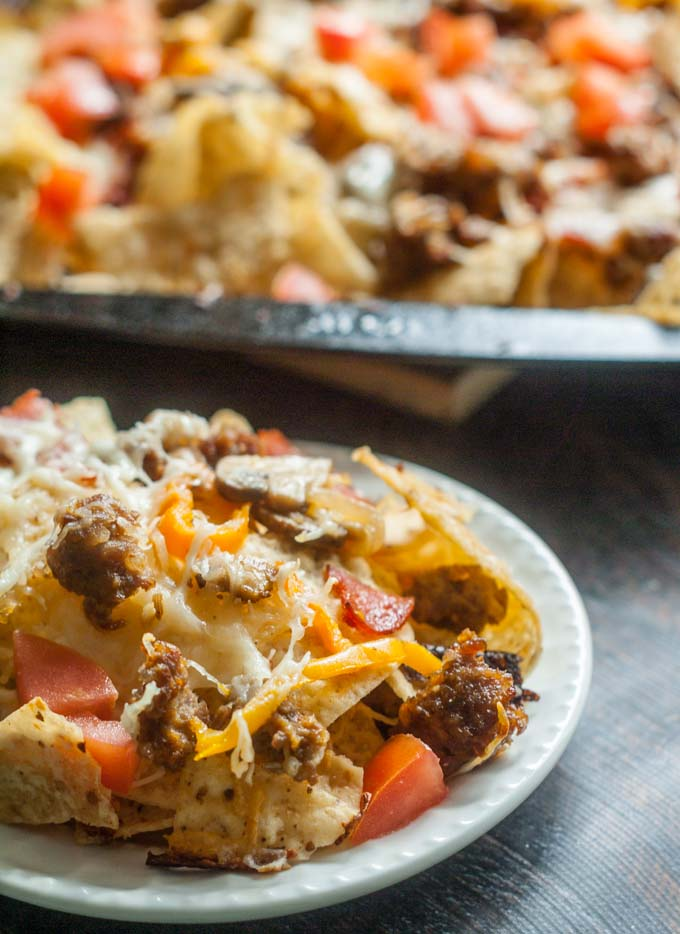 These easy sheet pan Italian style nachos are a fun twist on the usual. Packed with all the ingredients of a good sausage pizza or pasta but in sheet pan form so all can share.