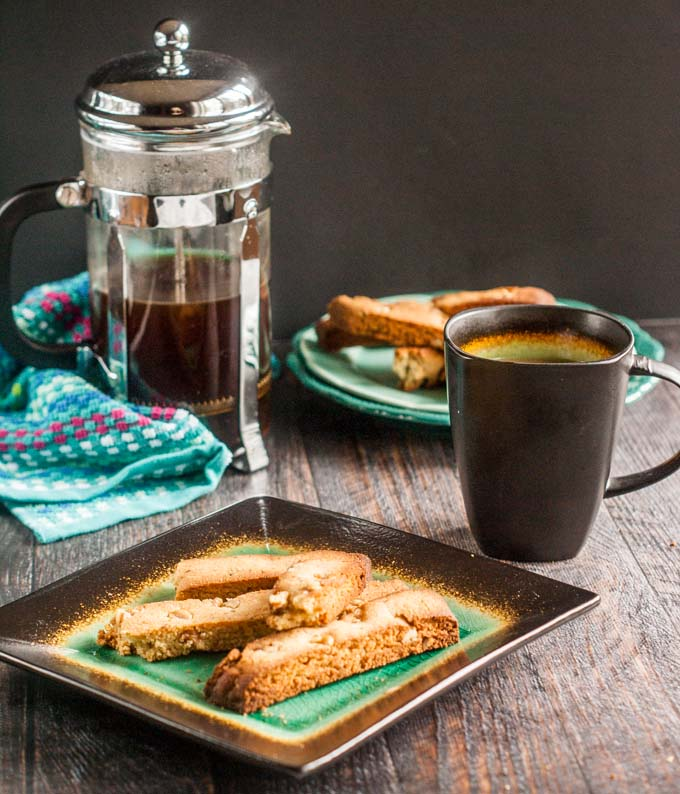green and black plate with gluten free biscotti and coffee press in background with a cup of coffee