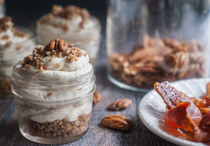 small jars with maple bacon low carb cheesecake, a plate of bacon and a jar of raw pecans