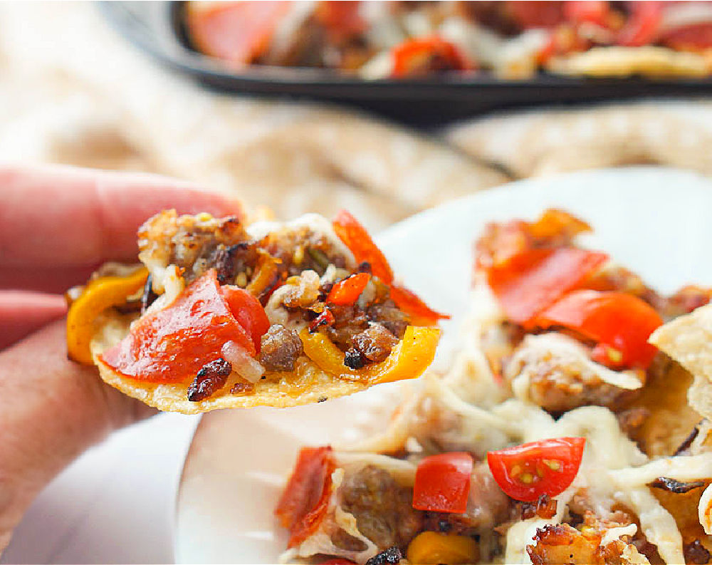 a hand holding a tortilla chip topped with Italian sausage, peppers and cheese