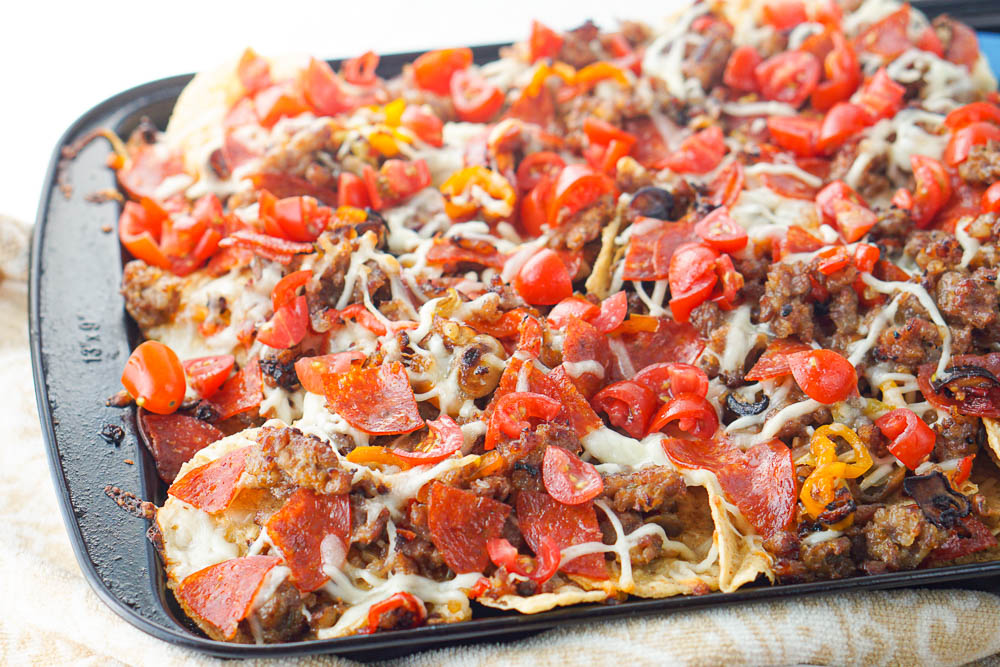 closeup of tortilla chips topped with sausage, peppers, pepperoni, cheese and tomatoes