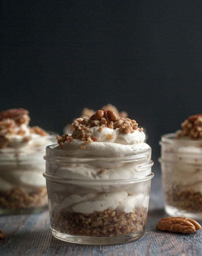 small jars with maple bacon low carb cheesecake and a few pecans scattered