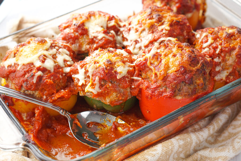 closeup of a tray of meatball stuffed peppers and a spoon