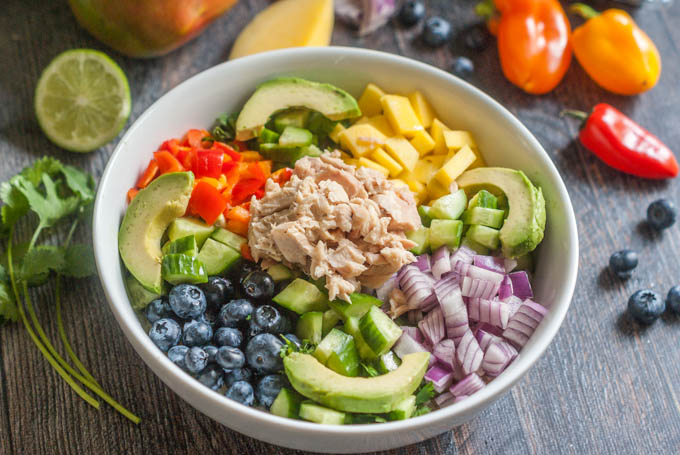 Paleo mango salsa bowl with tuna in a white bowl filled with colorful vegetables and fruit