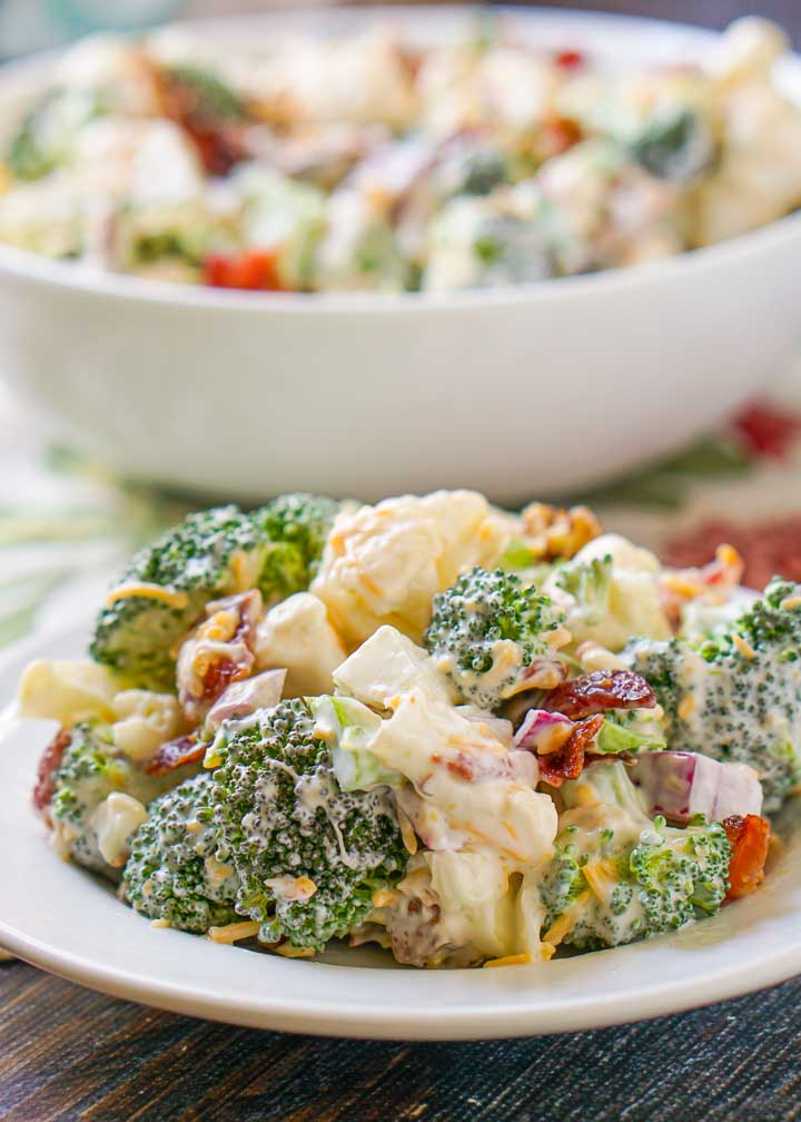 white plate with loaded keto broccoli cauliflower salad with a bowl in the background