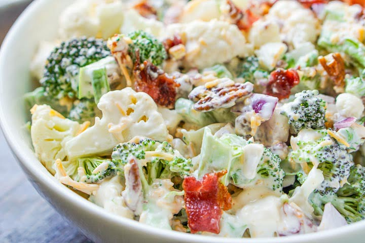 closeup of a white bowl with loaded low carb broccoli cauliflower salad with bacon