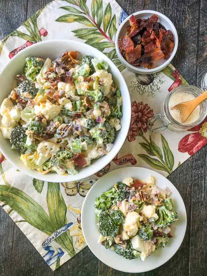 white bowl and white plate with loaded keto broccoli cauliflower salad with a bowl of bacon on floral cloth