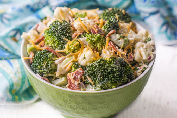 green bowl with broccoli cauliflower salad and blue tea towel in background