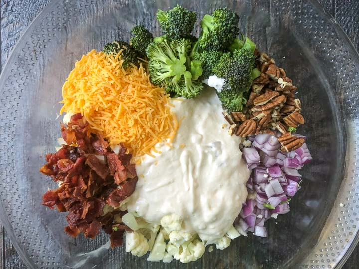 Ingredients in a glass bowl for broccoli salad: raw broccoli and cauliflower, cheddar cheese, bacon, pecans, red onion and dressing