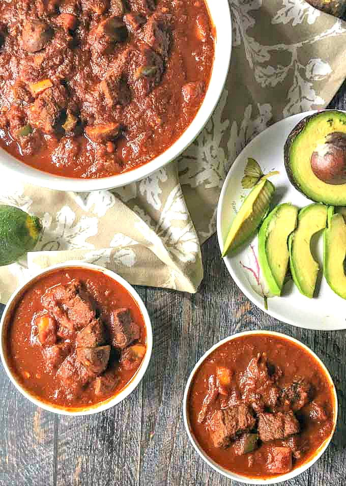 two small and one large white bowls with bean less beef chili and a sliced avocado on a plate