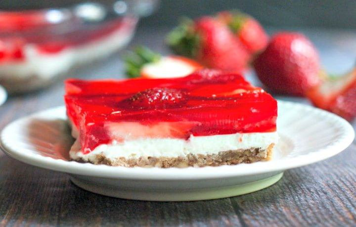 closeup of a piece of keto strawberry jello dessert with fresh strawberries in background