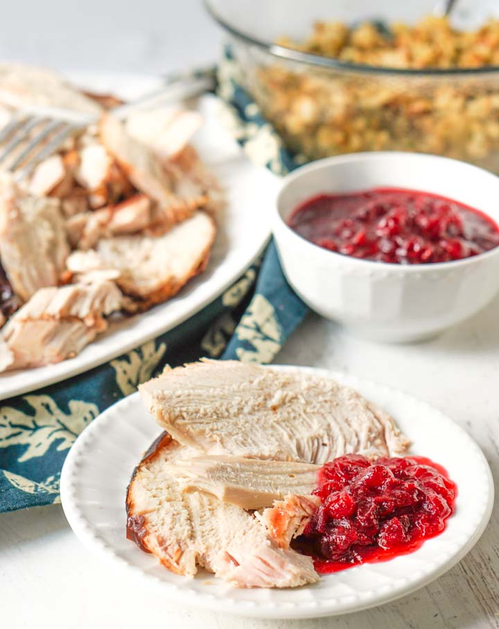 white plate with sliced smoked turkey breast with cranberry sauce and stuffing in background