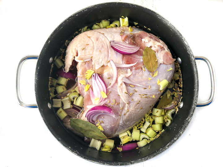 black pot with raw turkey breast in a brine with chopped celery, red onions and bay leaves