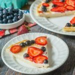 fathead fruit pizza with strawberries and blueberries on white plates and text overlay.