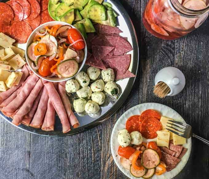 round silver relish tray with meats and cheese and a bowl and jar with pickled ratatouille vegetables.