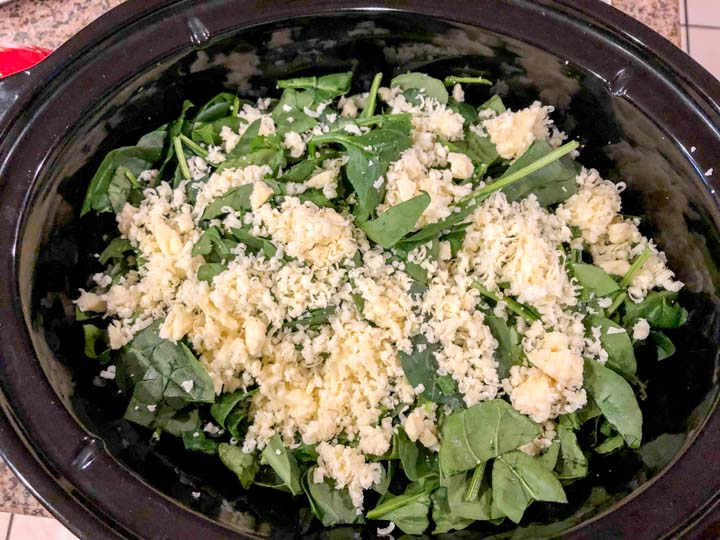 spinach and cheeses in crock before cooking