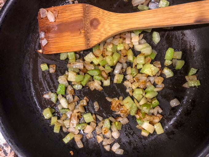 skillet with sauteed onions and celery with wooden spoon