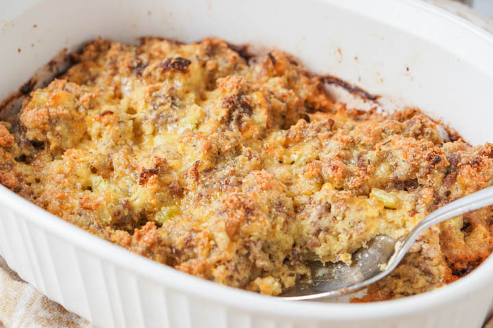 white baking dish with keto sausage stuffing with a silver spoon