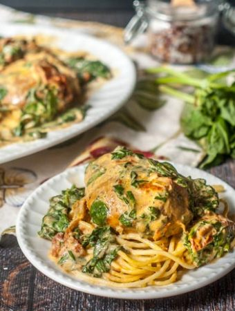 This slow cooker creamy tomato chicken & spinach dish is full of flavor and easy for a weeknight dinner. The rich and creamy sauce is perfect with the fresh spinach and chicken and only 3.3g net carbs!