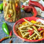 red bowl and jar with pickled green beans and text
