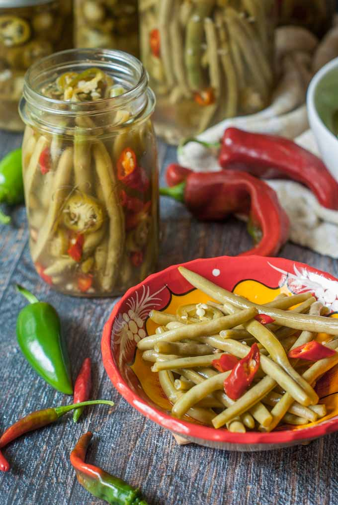 red bowl with some of the pickled green beans with the jars in the background and fresh peppers scattered about