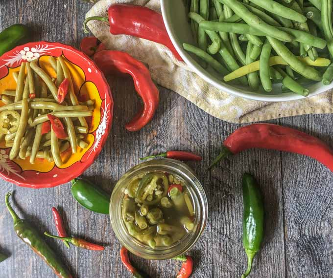 aerial view of a red bowl and jar with pickled green beans and a bowl of raw green beans and raw hot peppers