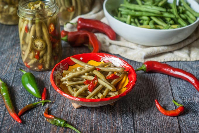 closeup of red bowl with pickled green beans