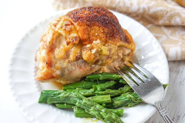low carb stuffed chicken thigh on white plate with asparagus