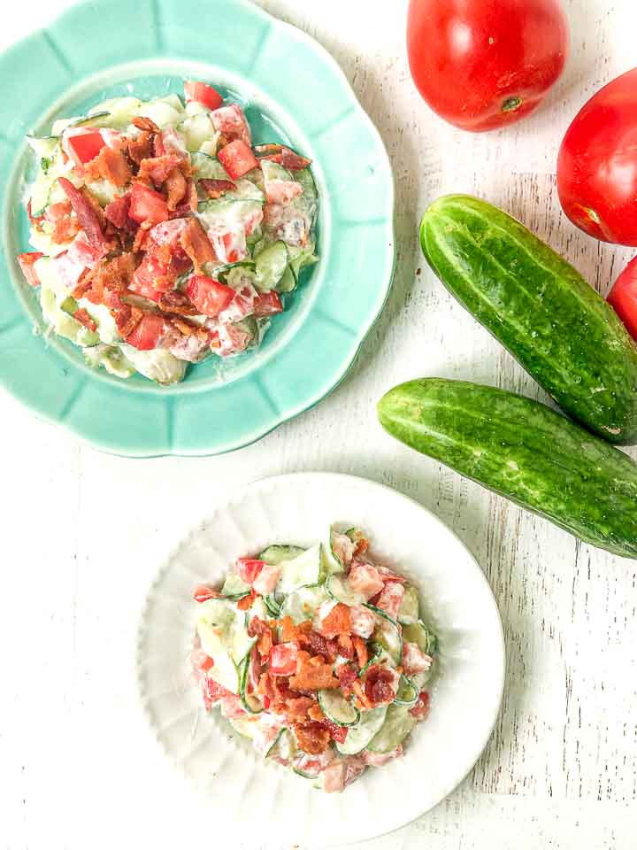 white and blue plate with the creamy cucumber salad and fresh tomatoes and cucumbers on the side