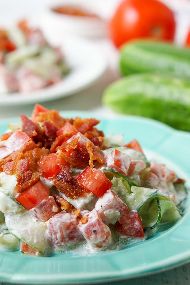 closeup of a blue plate with the creamy cucumber salad topped with bacon and fresh tomatoes and cucumbers in the background