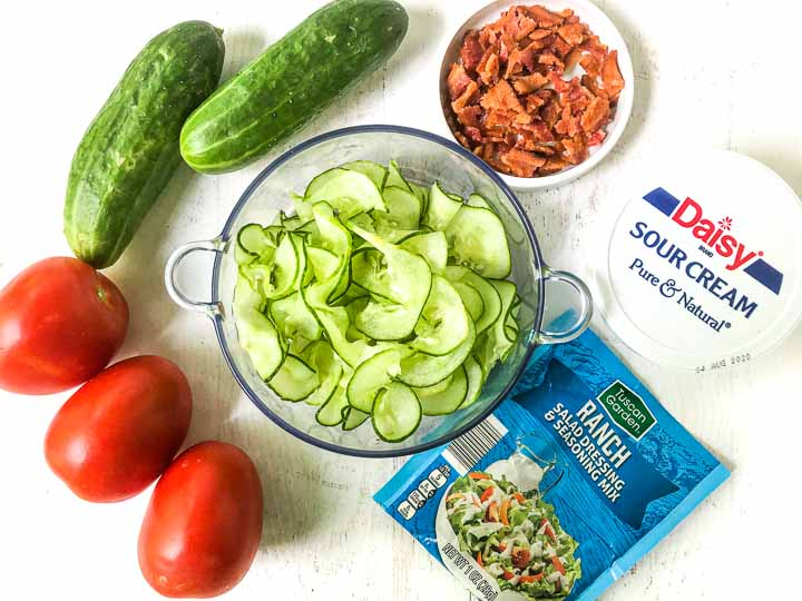 ingredients to make this creamy cucumber salad: cucumbers, Roma tomatoes, bacon, sour cream and ranch mix