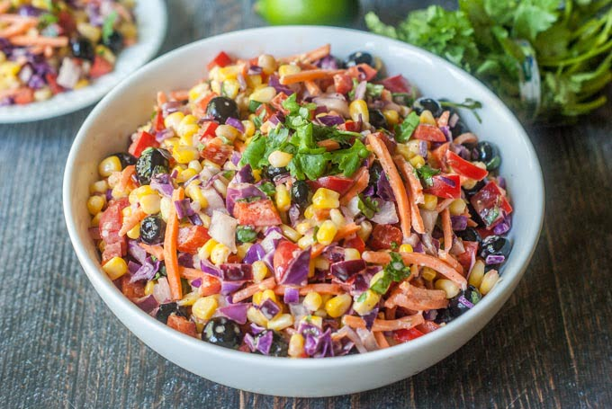 This rainbow Mexican corn salad is a tasty twist on Mexican corn. Colorful vegetables and fruit are tossed in a creamy lime dressing for the perfect sweet and tangy salad. A beautiful and tasty side dish for picnics and parties.