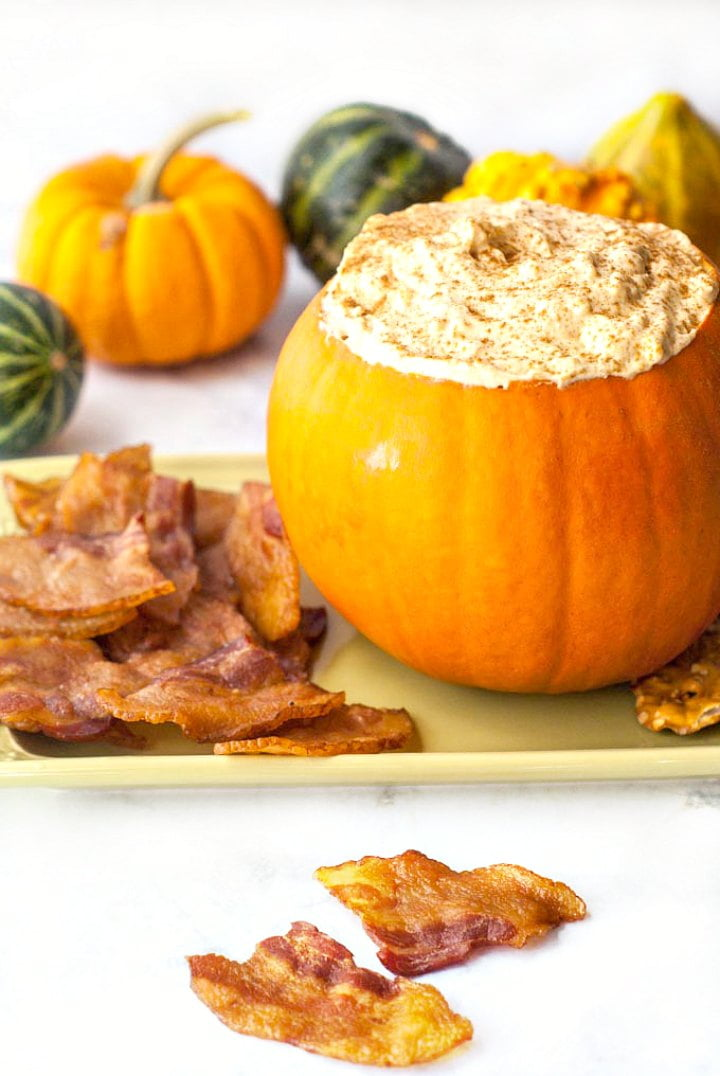 pumpkin with cheese cake dip and bacon chips in front and on platter