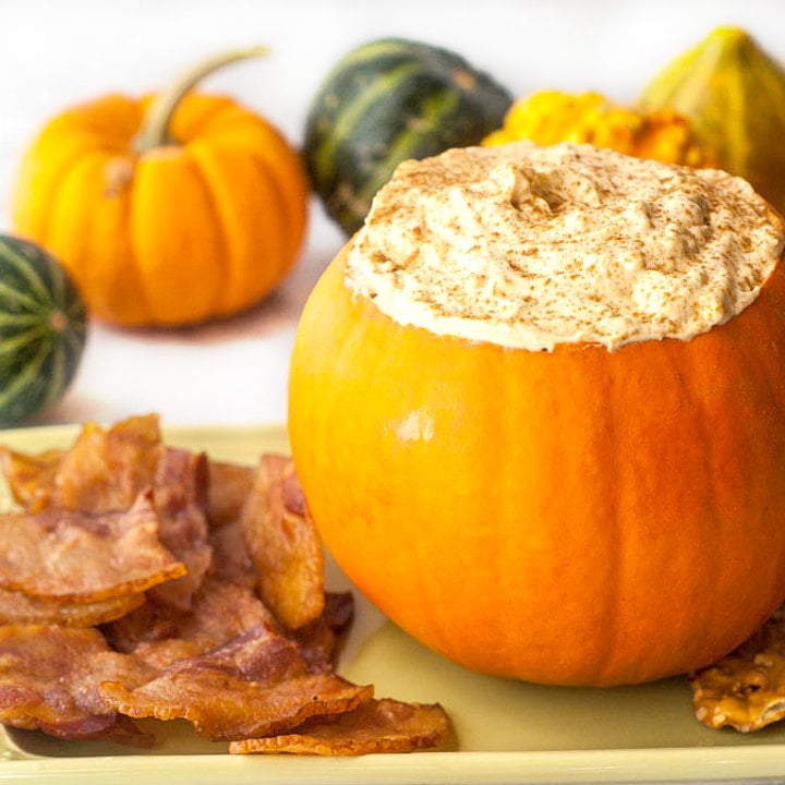 pumpkin filled with keto pumpkin cheesecake dip with bacon chips and gourds in the background