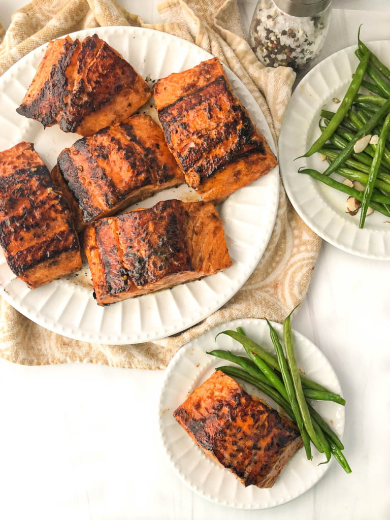 aerial view of large and small white plates with Asian glazed salmon with green beans