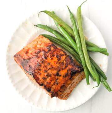 white plate withe a piece of keto Asian salmon and a few green beans
