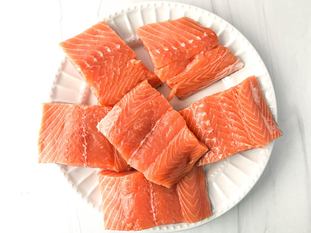 white plate with raw salmon filets