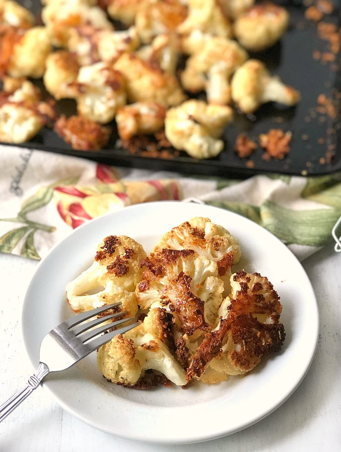 white plate with parmesan coated cauliflower bites with cookie sheet in background