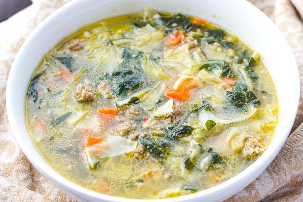 closeup of a big bowl of low carb sausage soup with cabbage