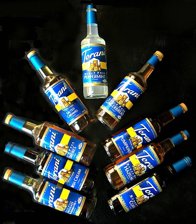9 bottles of Torani sugar free syrups forming a tree on a black background