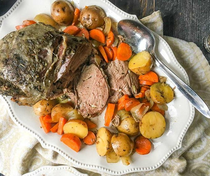 white platter with slow cooker lamb roast and potatoes, carrots and a big spoon