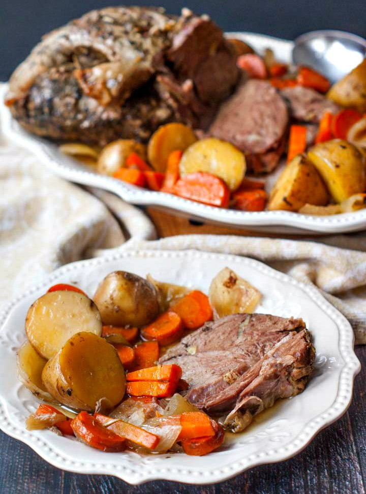 white platter and plate with slow cooker lamb roast and vegetables