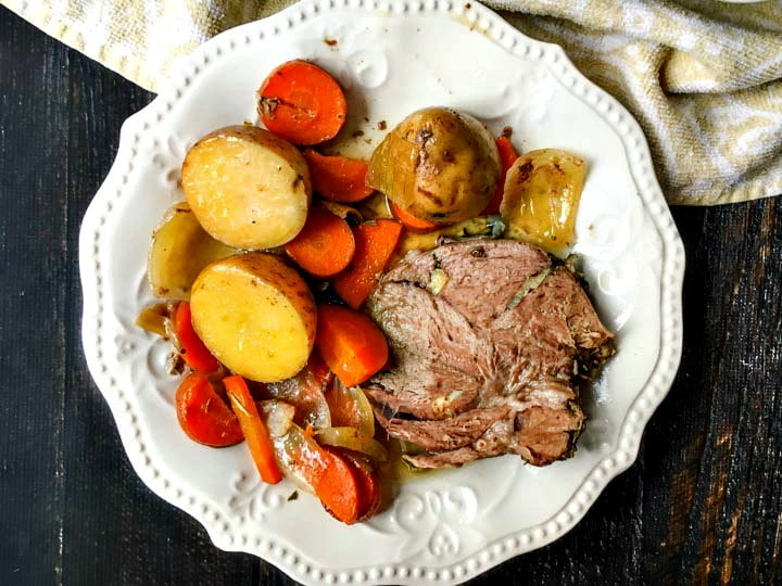 white plate with a slice of lamb roast and potatoes, carrots and a big spoon