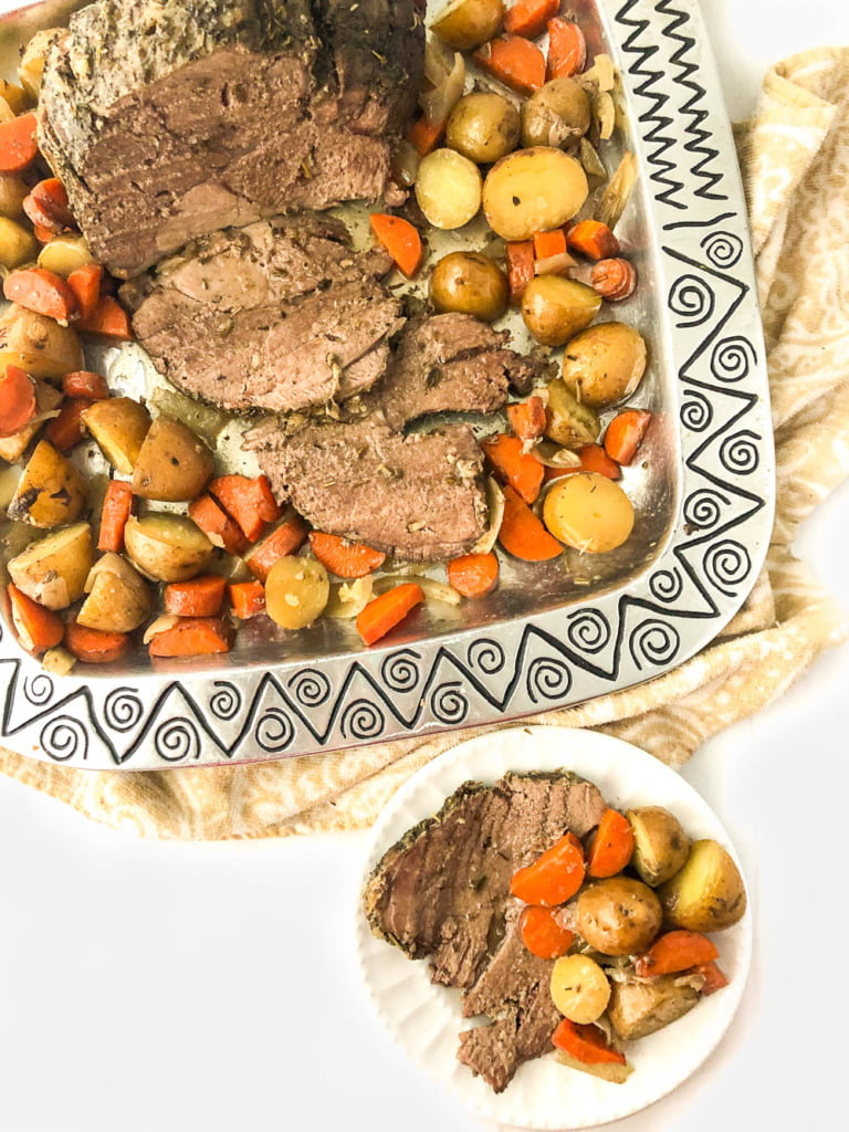 aerial view of a metal platter with a lamb roast and scattered roasted potatoes and carrots