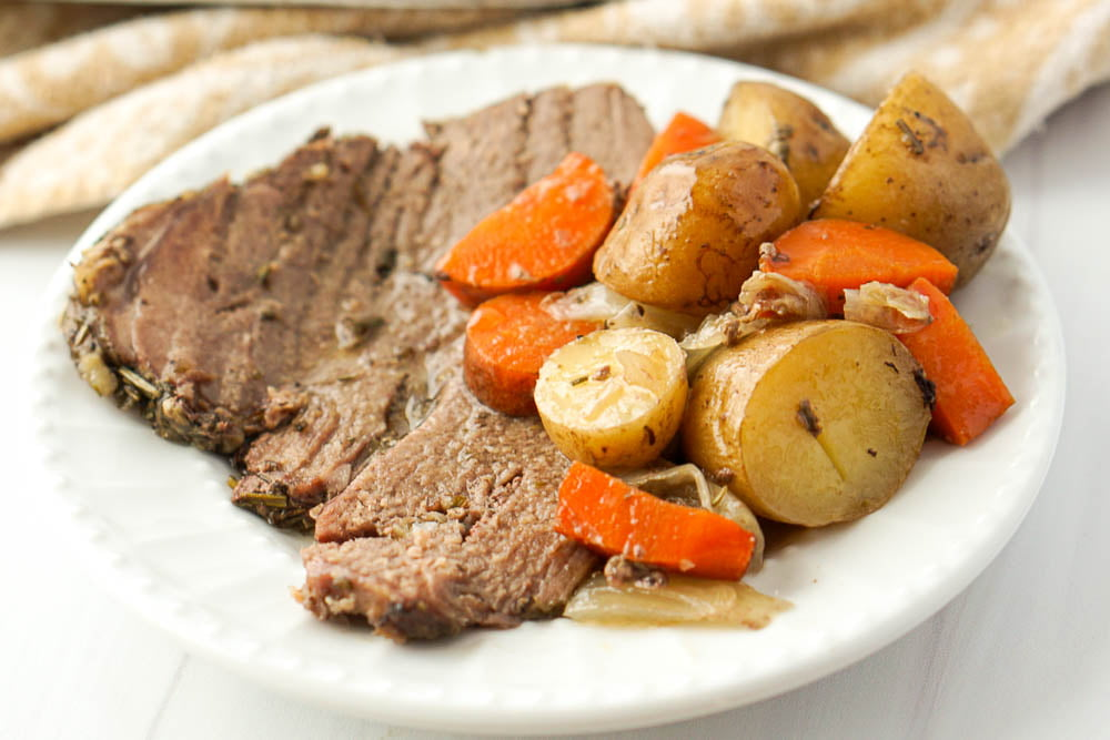 a white plate with a slice of lamb roast and some roasted veggies