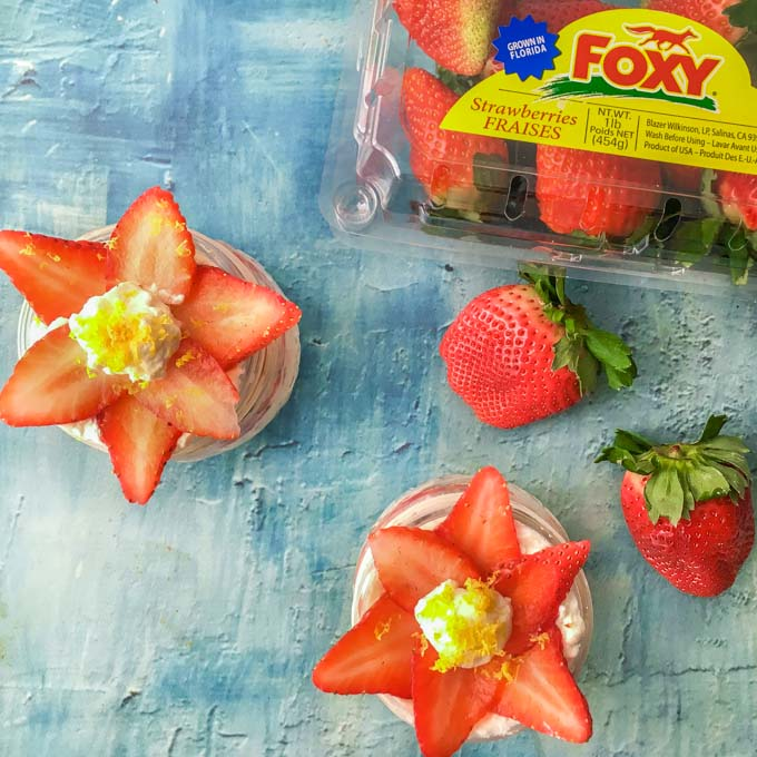 a box of strawberries with two no bake cheesecake desserts decorated with strawberry slices and lemon zest