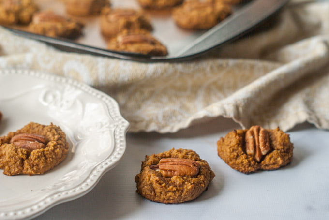 healthy pumpkin breakfast cookies on counter with plate and cookie tray in background